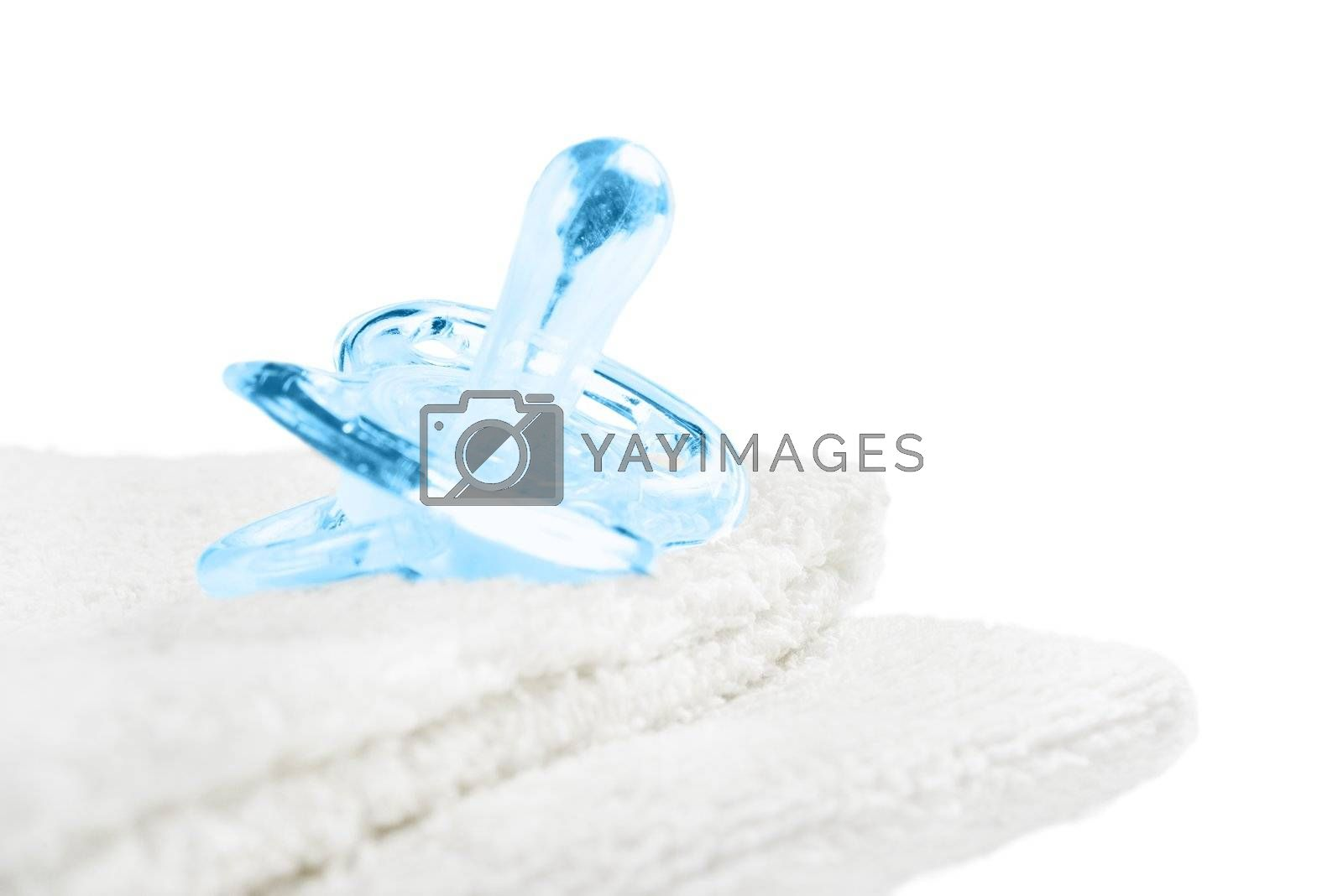 Baby pacifier on towel. Isolated on white.