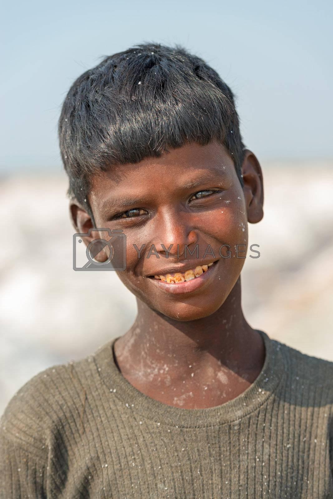 Sambhar, India - Nov 19: Portrait of indian kid in salt farm on Nov 19, 2012 in Sambhar Salt Lake, India. It is India's largest saline lake and where salt has been farmed for a thousand years.