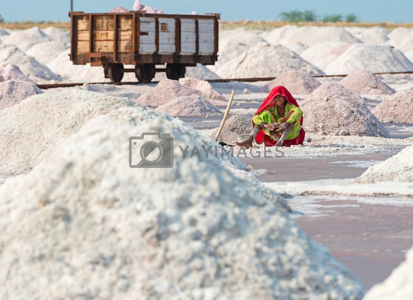 Sambhar, India - Nov 19: Female worker rests in salt farm on Nov 19, 2012 in Sambhar Salt Lake, India. It is India's largest saline lake and where salt has been farmed for a thousand years.
