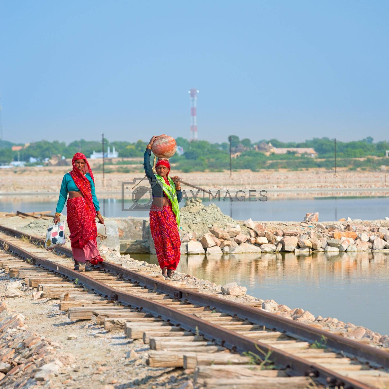 Sambhar, India - Nov 19: Female indian workers go along railway on Nov 19, 2012 in Sambhar Salt Lake, India. It is India's largest saline lake and and where salt has been farmed for a thousand years.