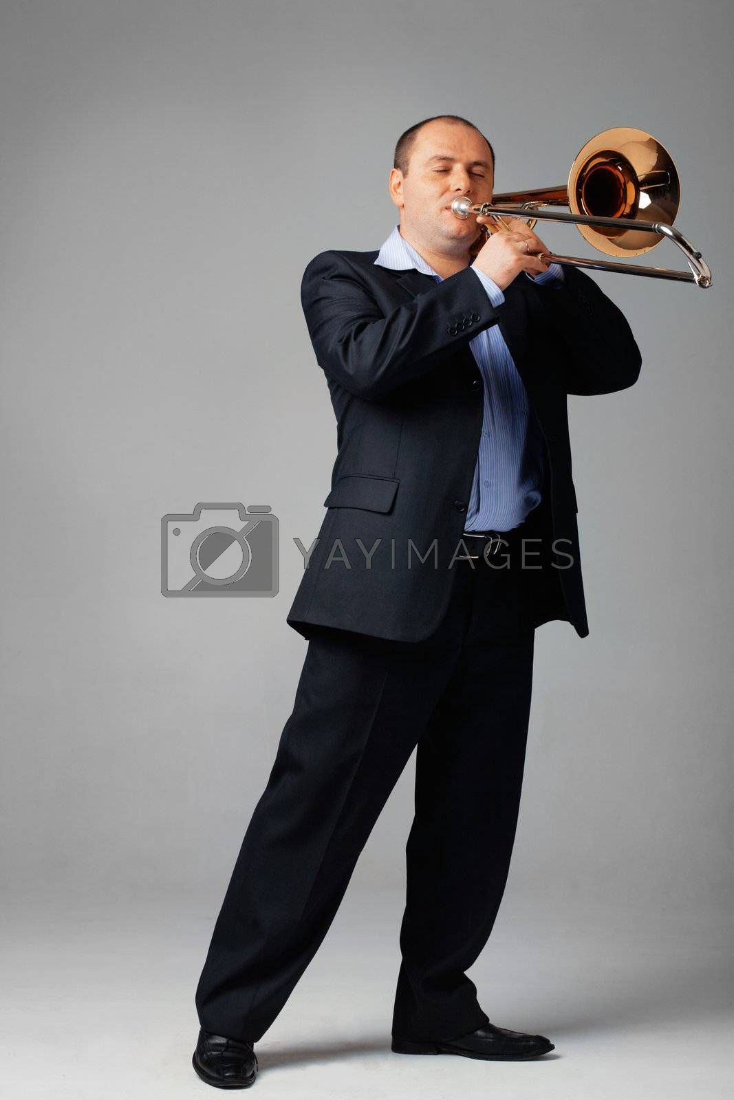 Portrait of a young man playing his trombone.