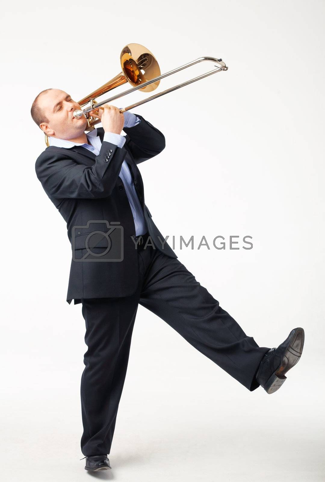 Portrait of a young man playing his trombone on white