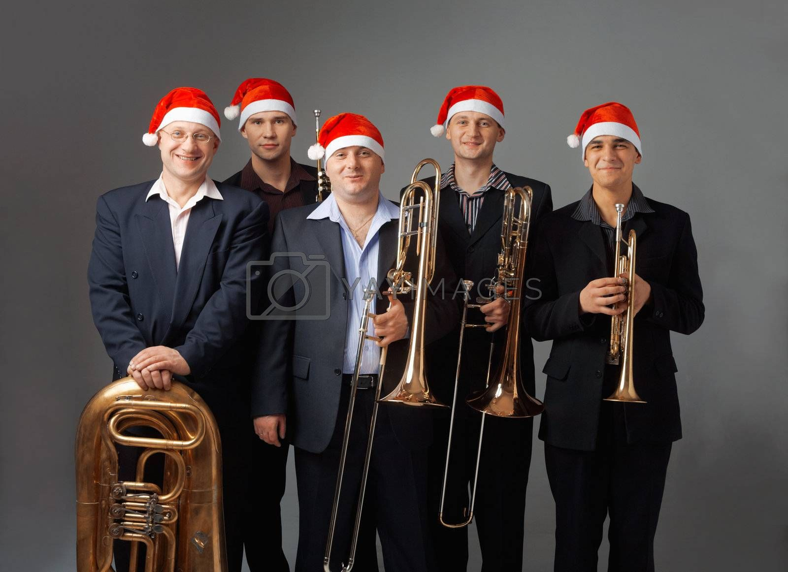 Portrait of a five young musicians with  instruments. They are dressed in a cap of Santa