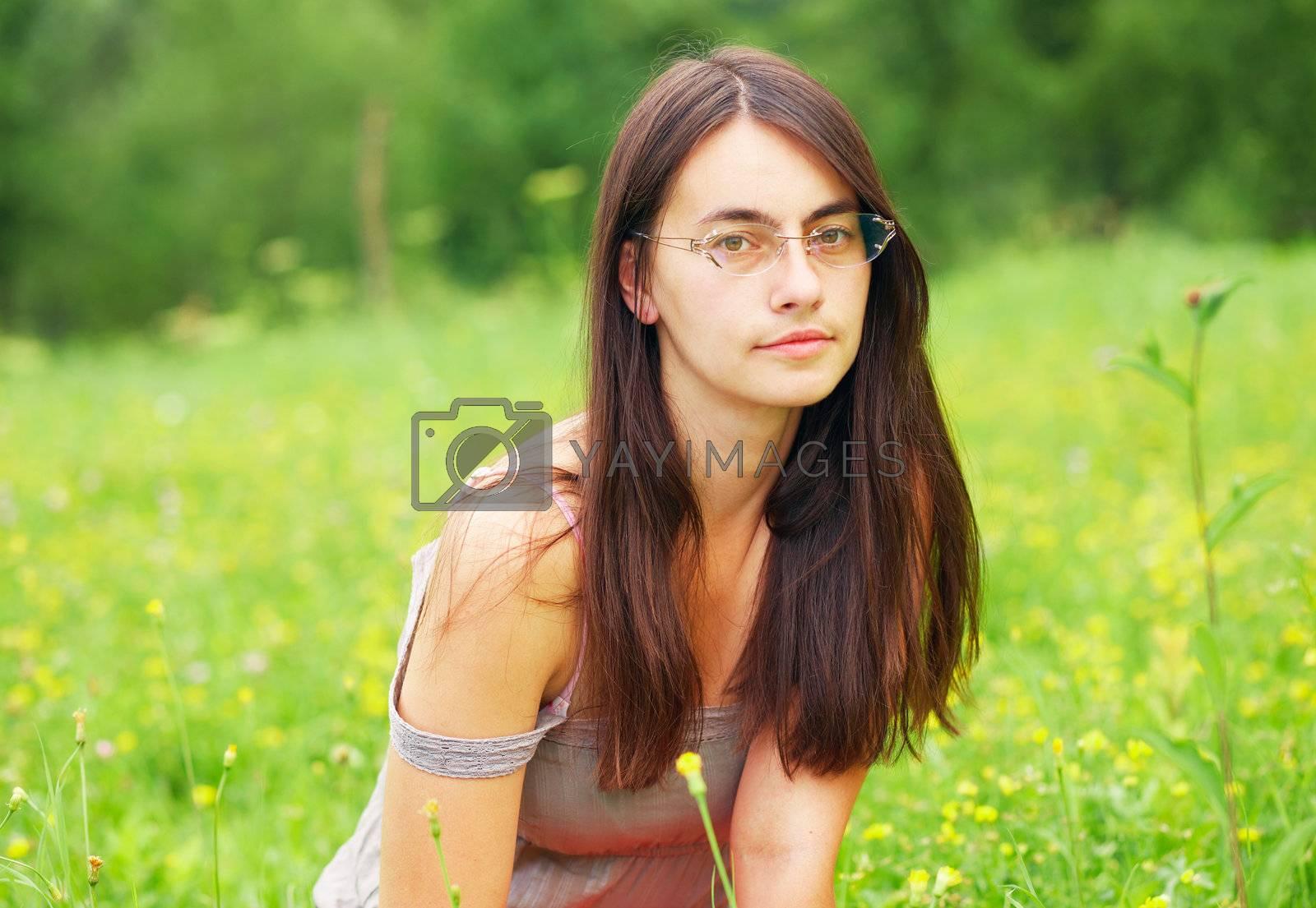 Portrait of a woman. She is sitting in a green meadow