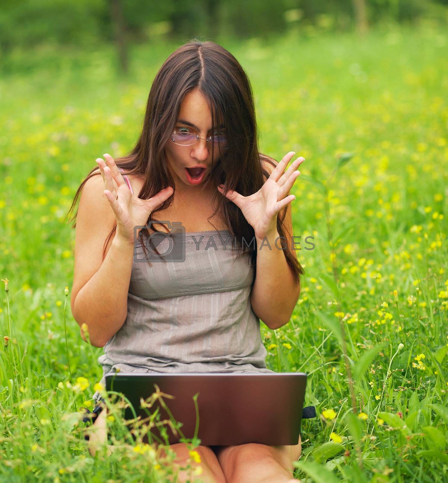 Shocked Young woman using her laptop outdoors.