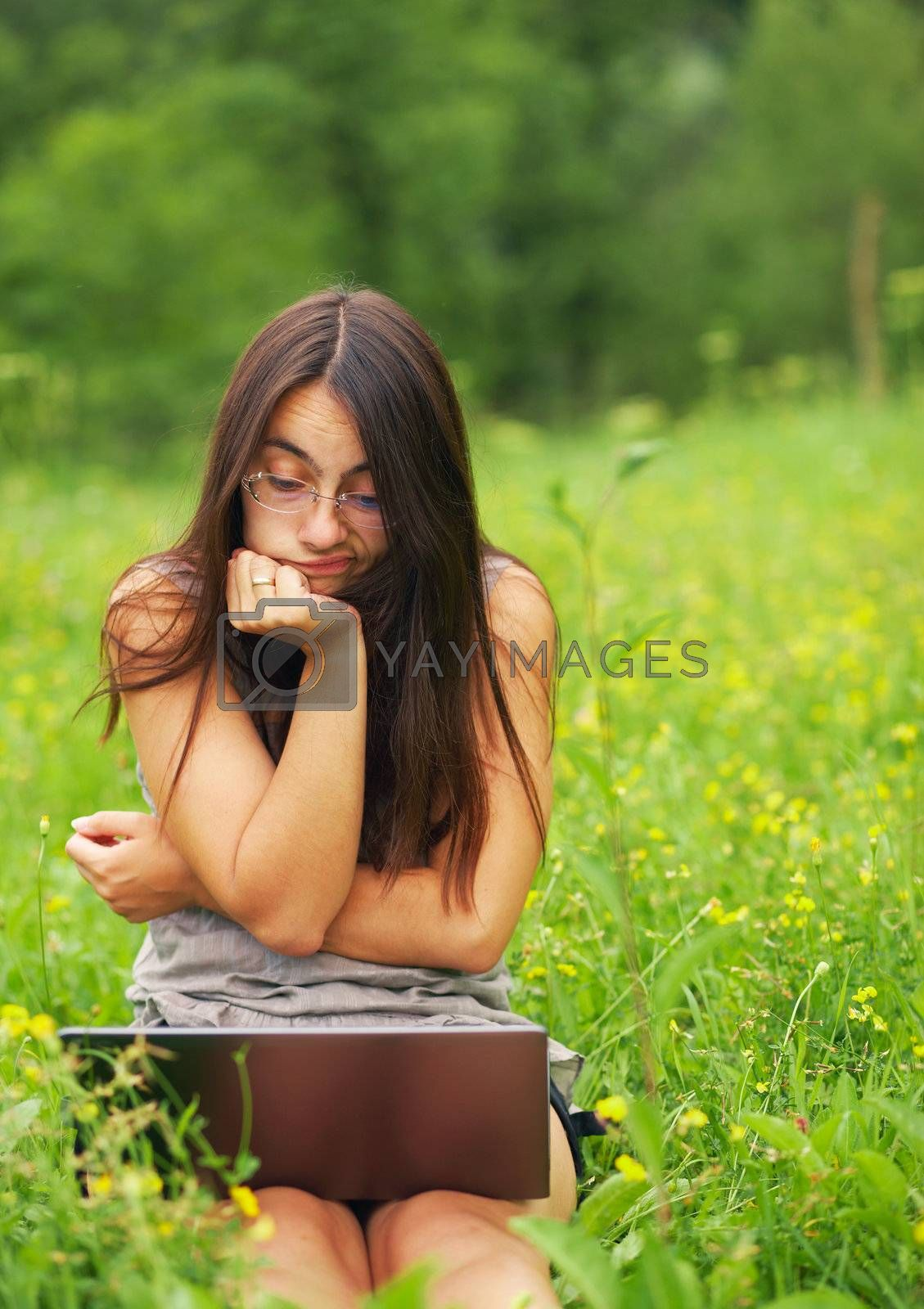 Worried young woman using her laptop outdoors.