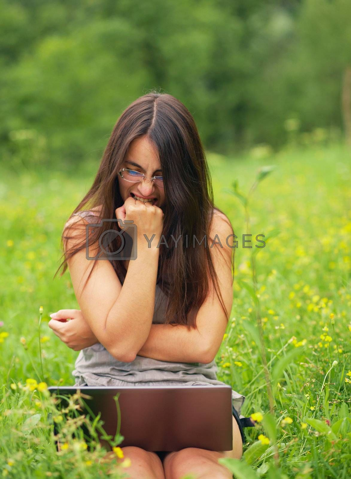 Angry young woman using her laptop outdoors.