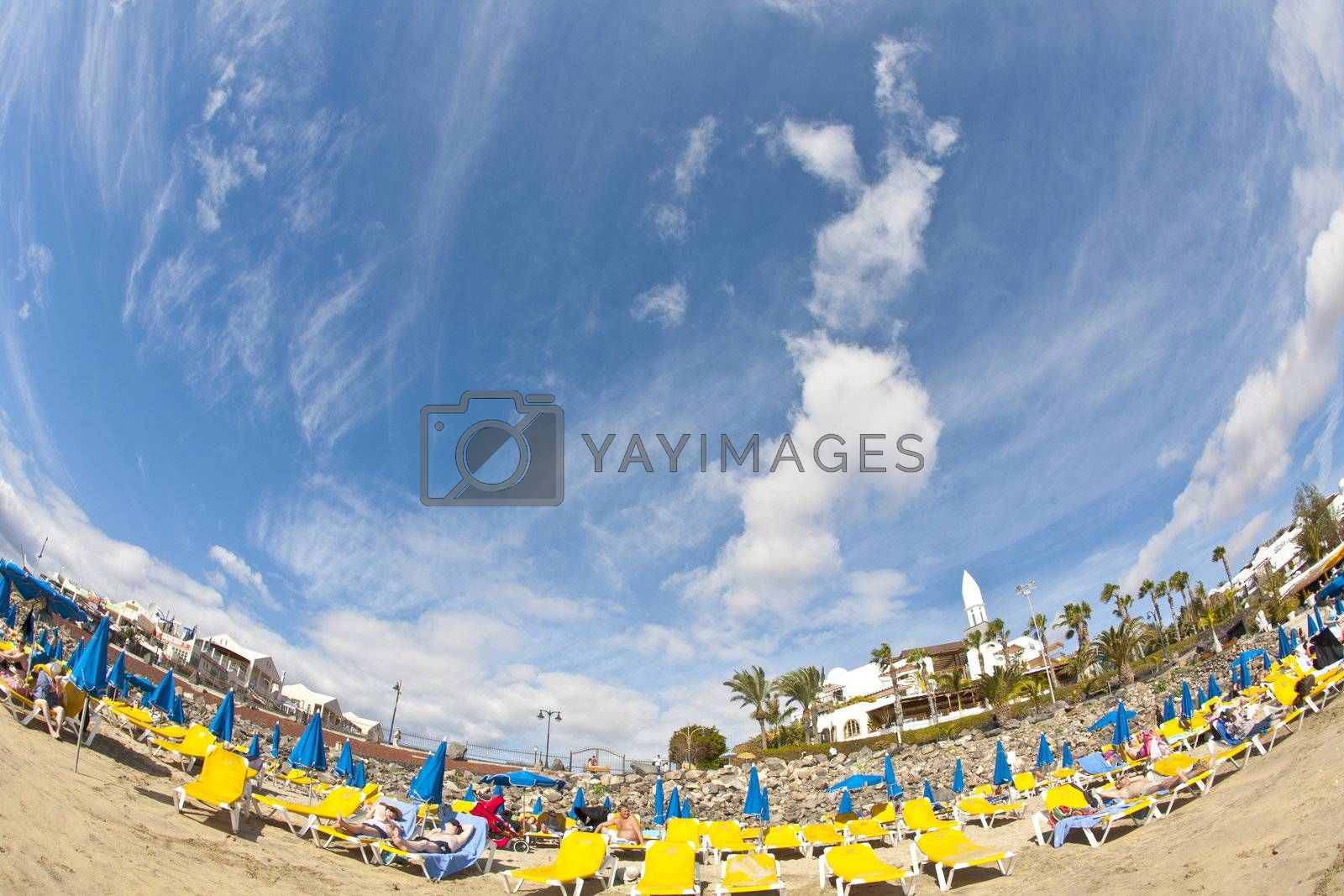 PLAYA BLANCA, SPAIN - JAN 1: people enjoy lying at the Beach Playa Dorada on January 01,2011 in Playa Blanca, Spain. The artifical beach was renovated in 2010 with additional white sand.