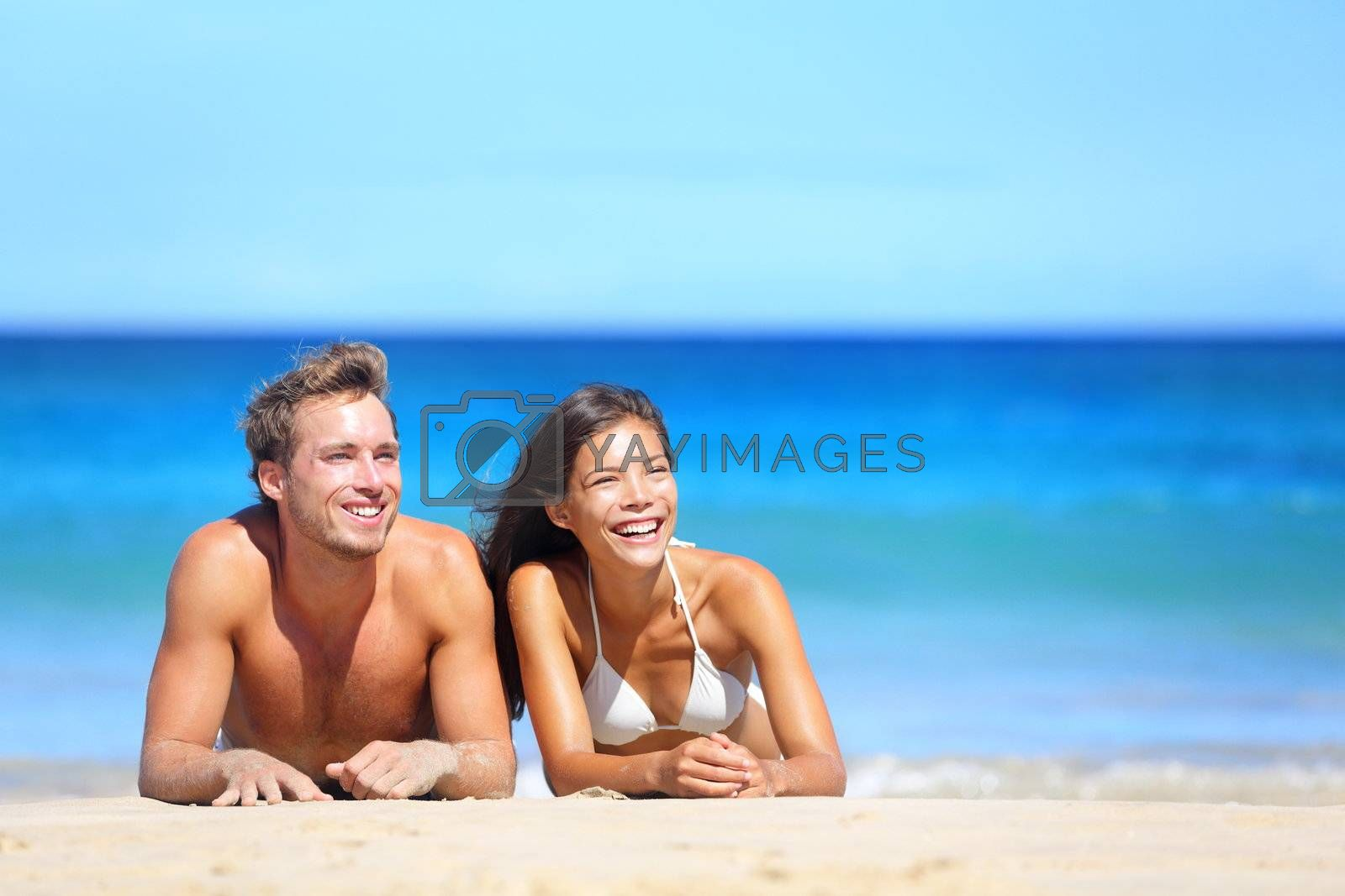 Beach couple looking. Happy multiethnic young couple lying on sand under sunny summer sun. Travel holidays concept. Caucasian man, Asian woman on hawaii.