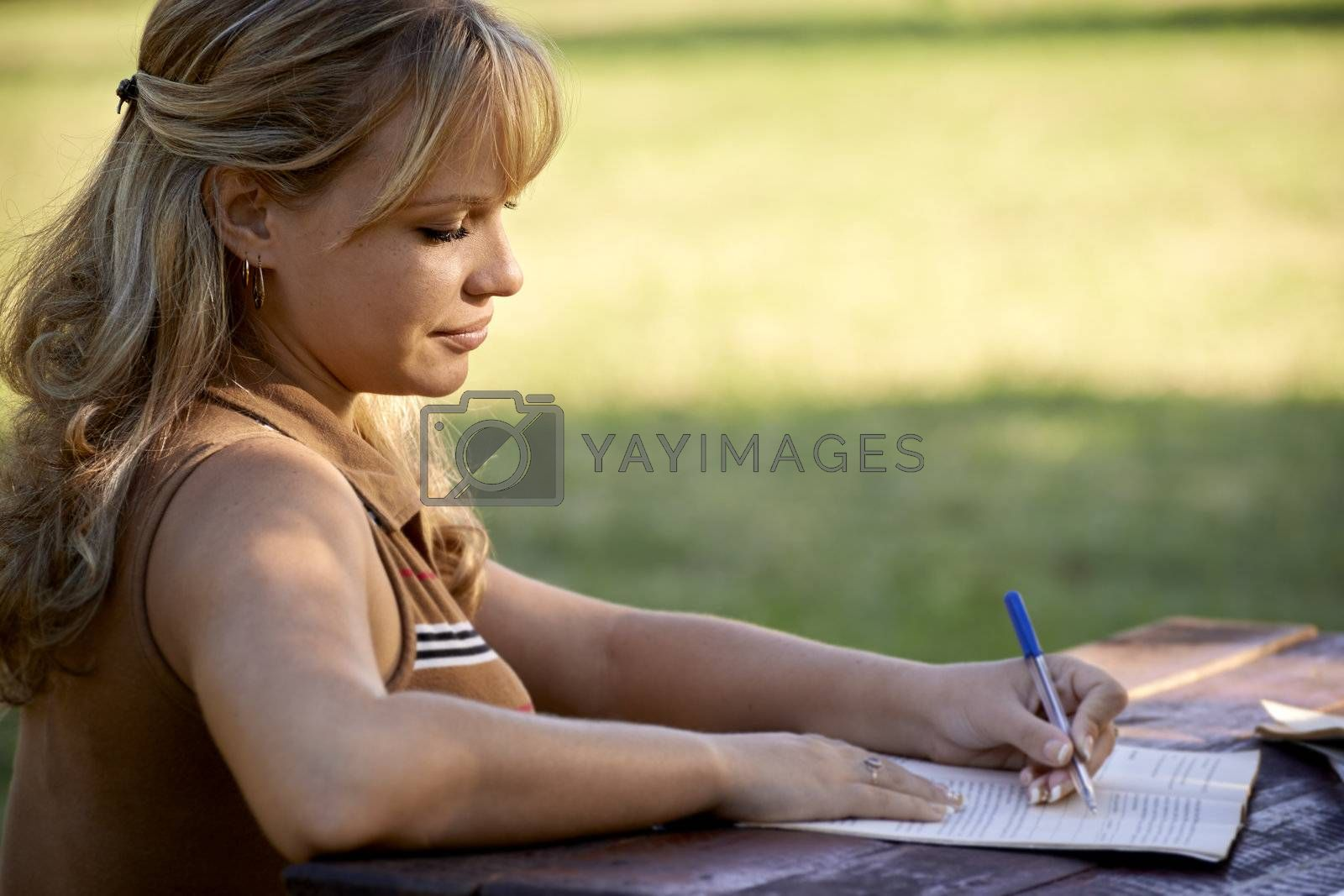 Young women and education, female student studying for college exam in park. Side view, copy space