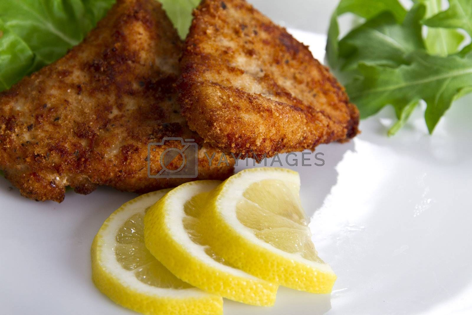 Breaded meat with lemon and salad