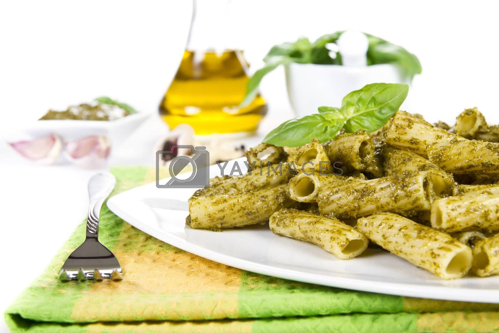 Pasta with pesto sauce and ingredients over white