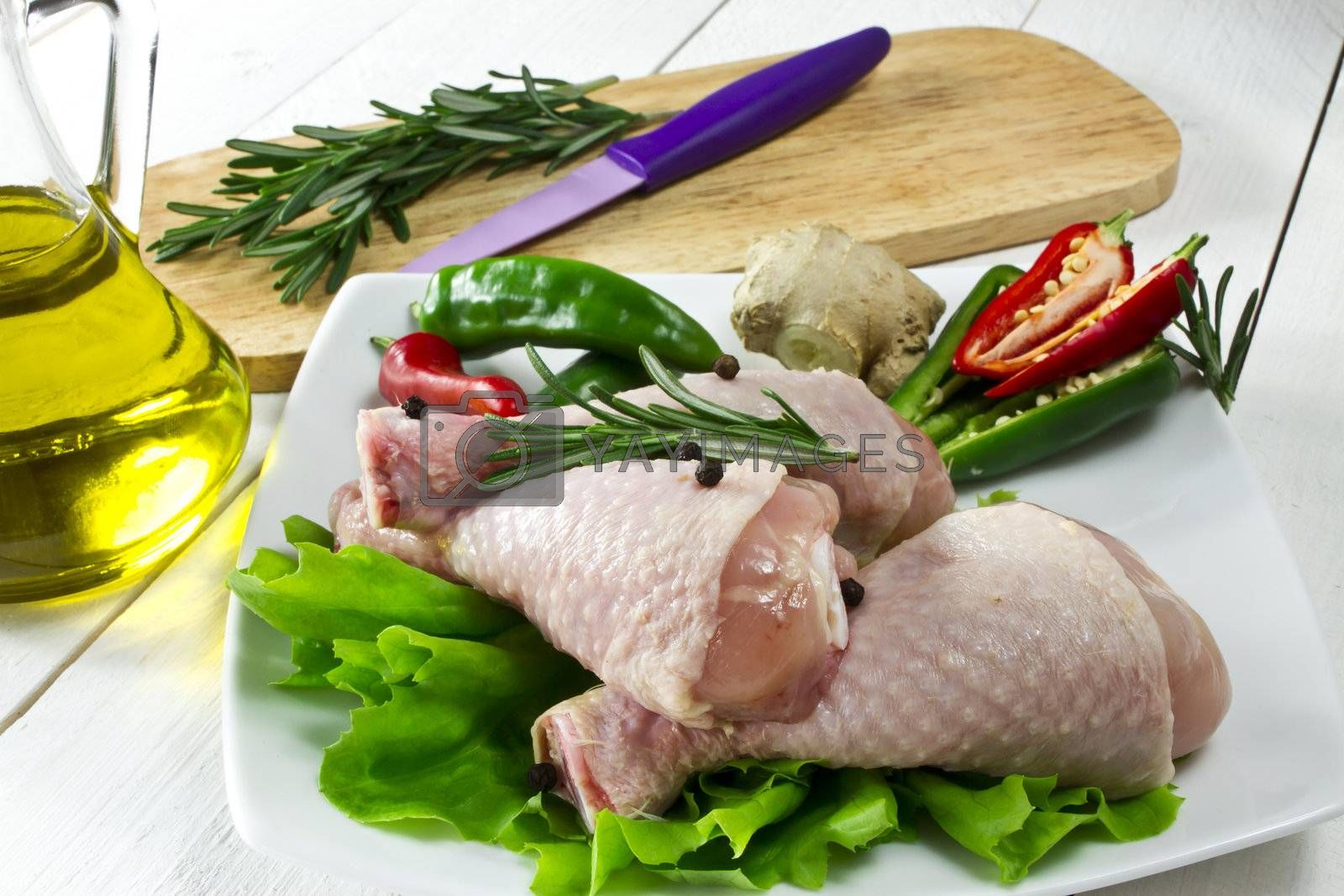 Fresh - raw chicken drumsticks on the plate