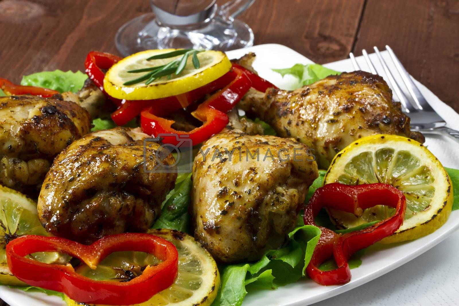 Fried chicken drumsticks with lemon and red peppers