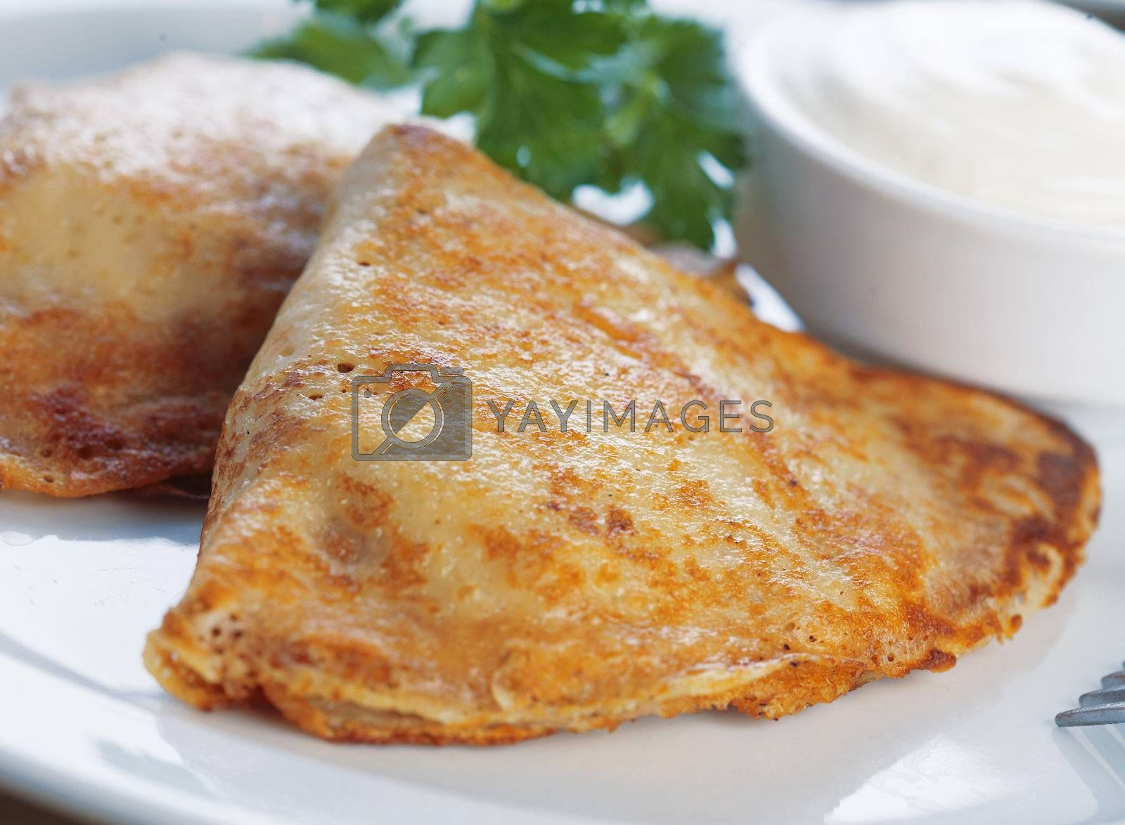Close-up of two pancakes stuffed with meat on the plate with mayonnaise and parsley.