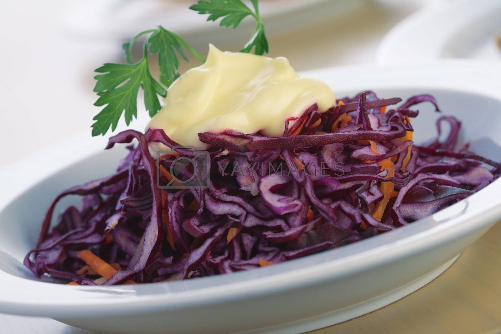 Close-up picture of a salad from red cabbage with mayonnaise and parsley.