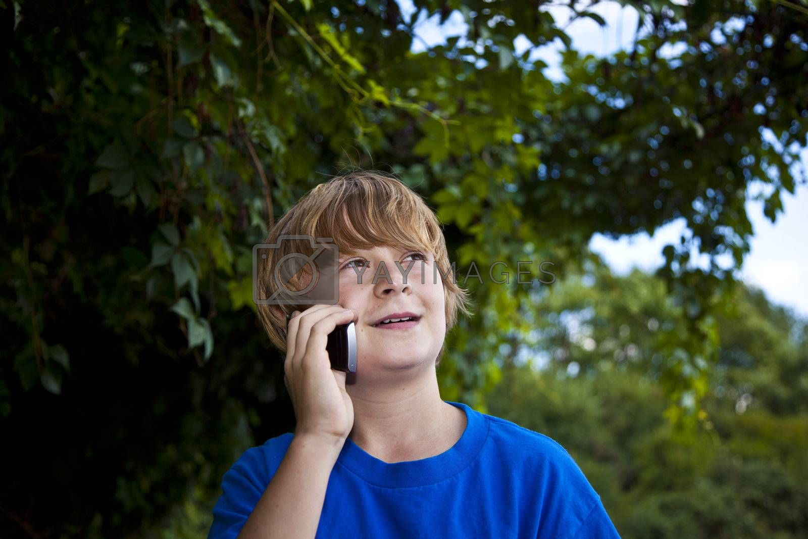 A young boy talking on a cell phone.