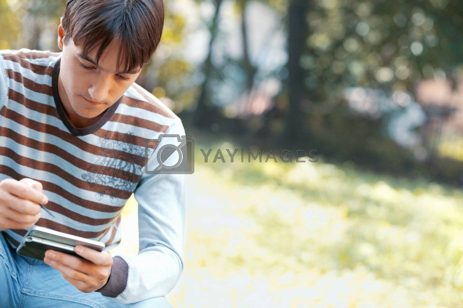 Young man using a PDA outdoors