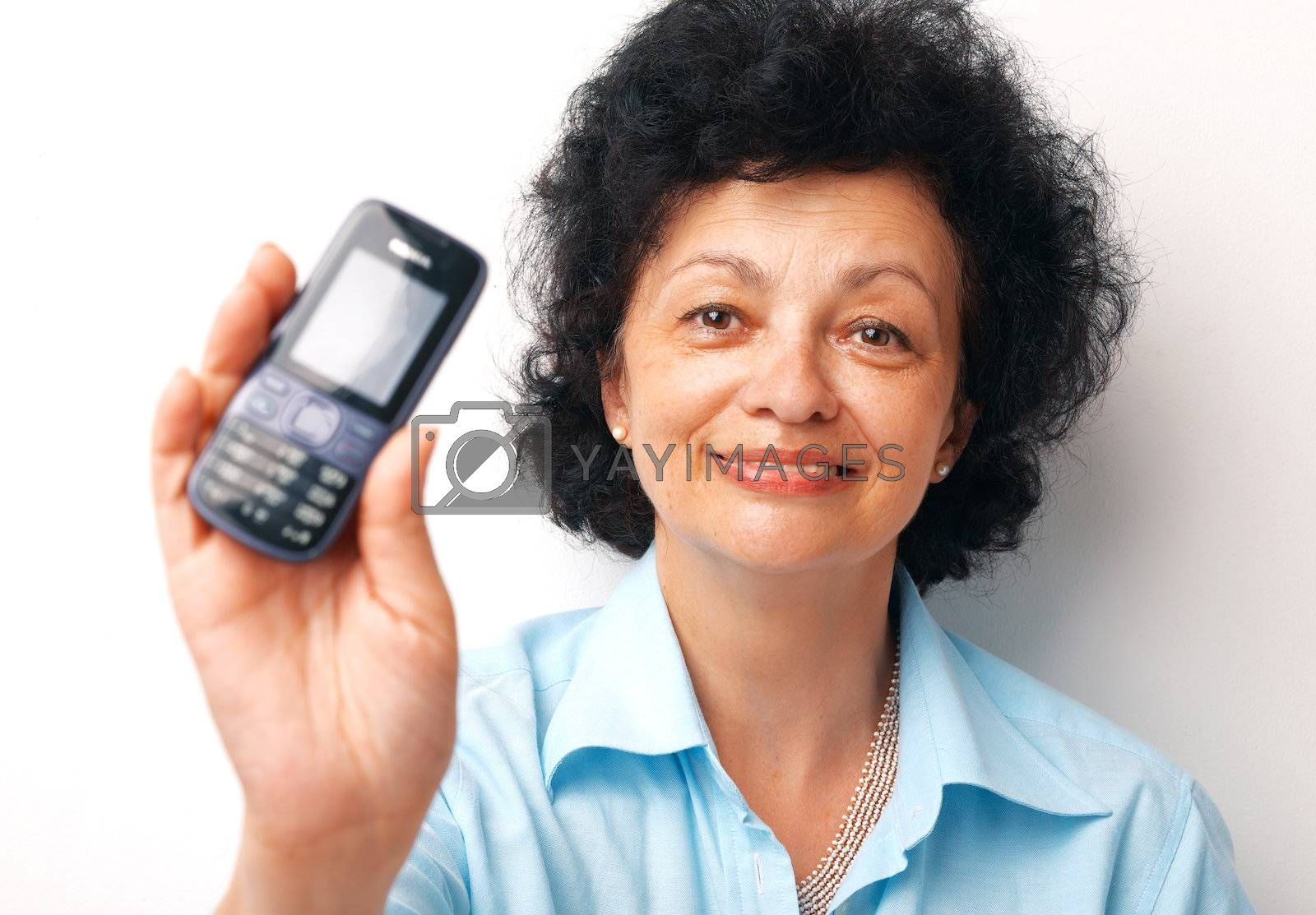 Close-up of an elder smiling woman holding and showing her mobile.