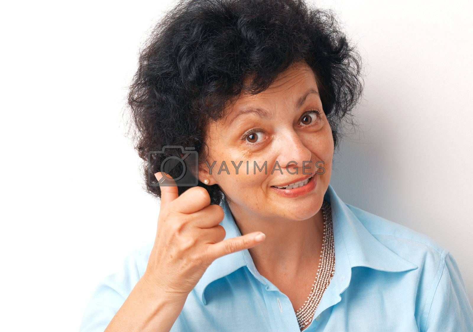 """Close-up of an elder woman showing a sign """"call me"""" over white background."""