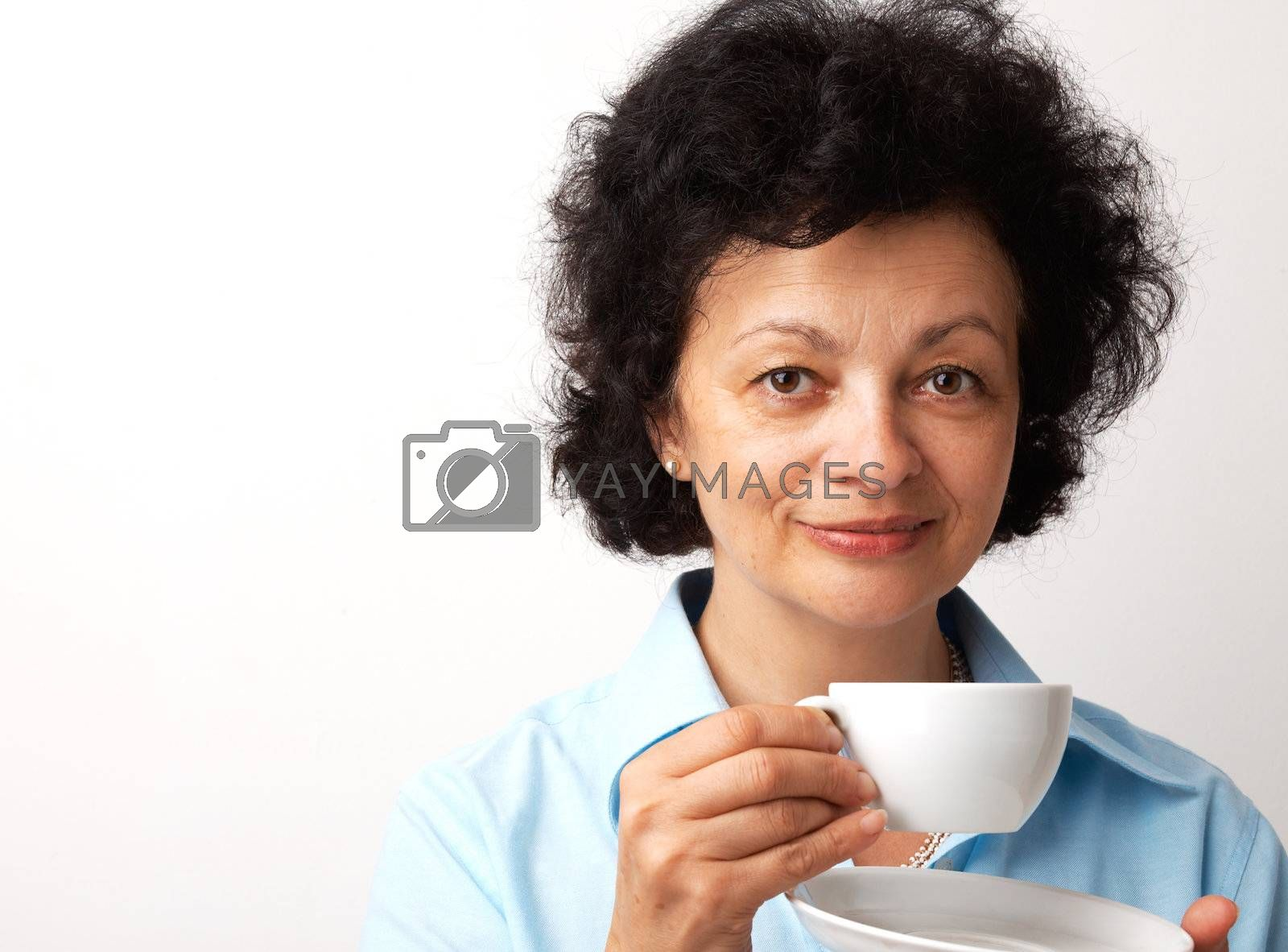 Close-up portrait of an elder smiling woman holding cup and saucer.