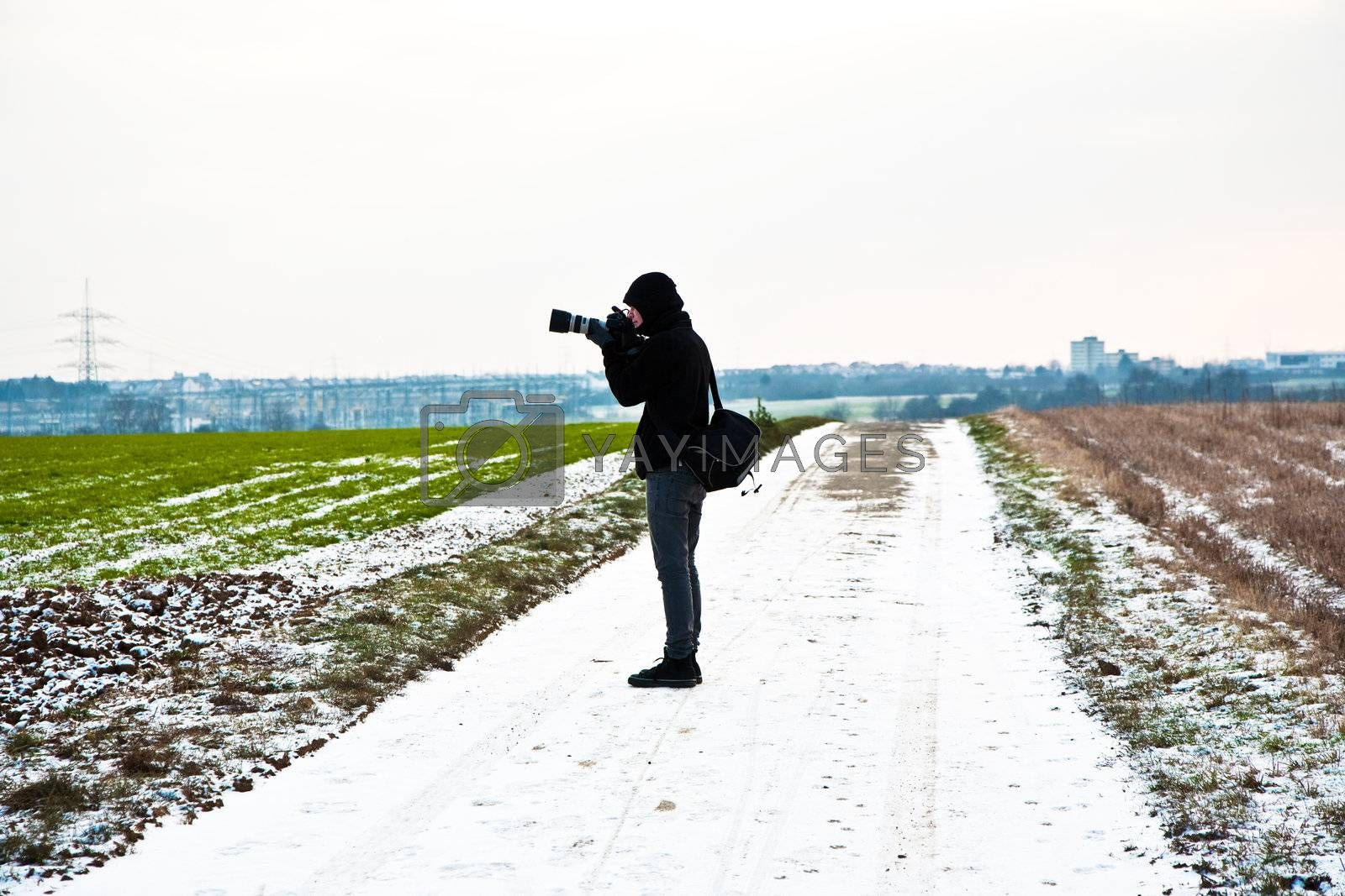 boys taking pictures of acres with snow in winter in beautiful light and structure