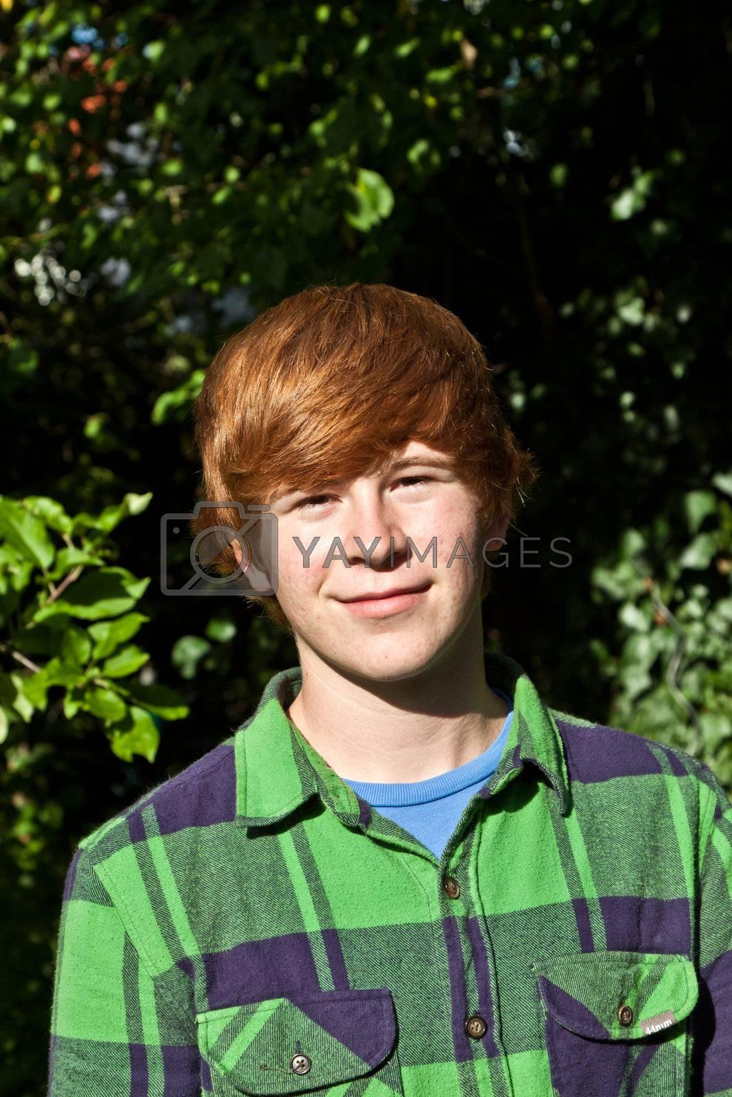 portrait of attractive happy smiling boy in the garden