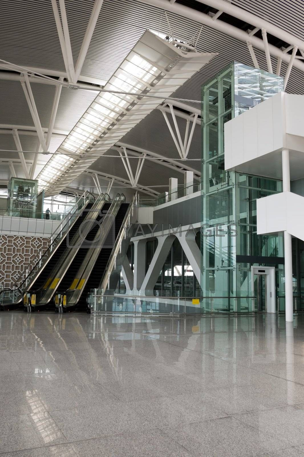 Modern business building interior with escalators and elevator