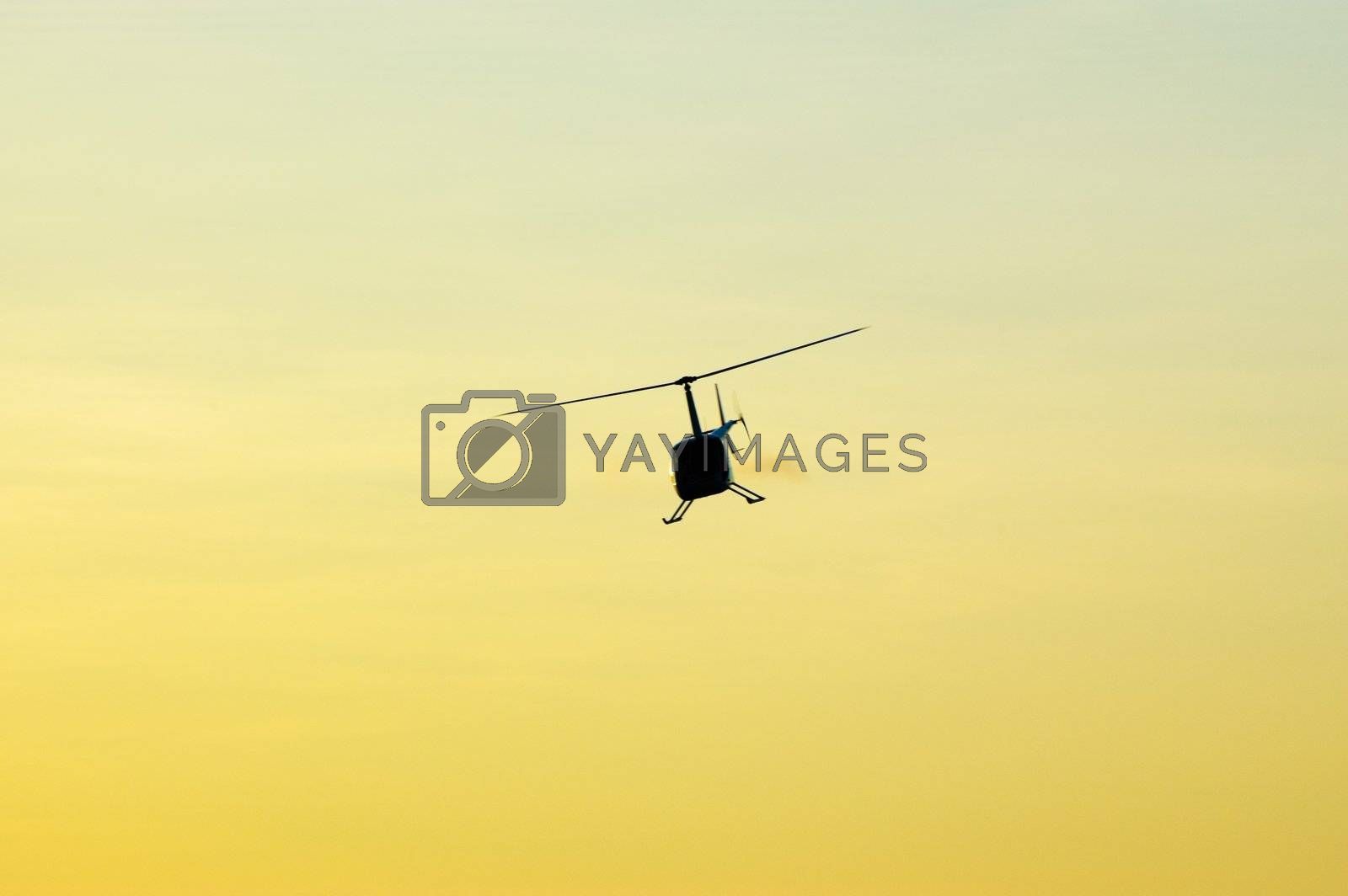 Helicopter flying over the sky at sunset