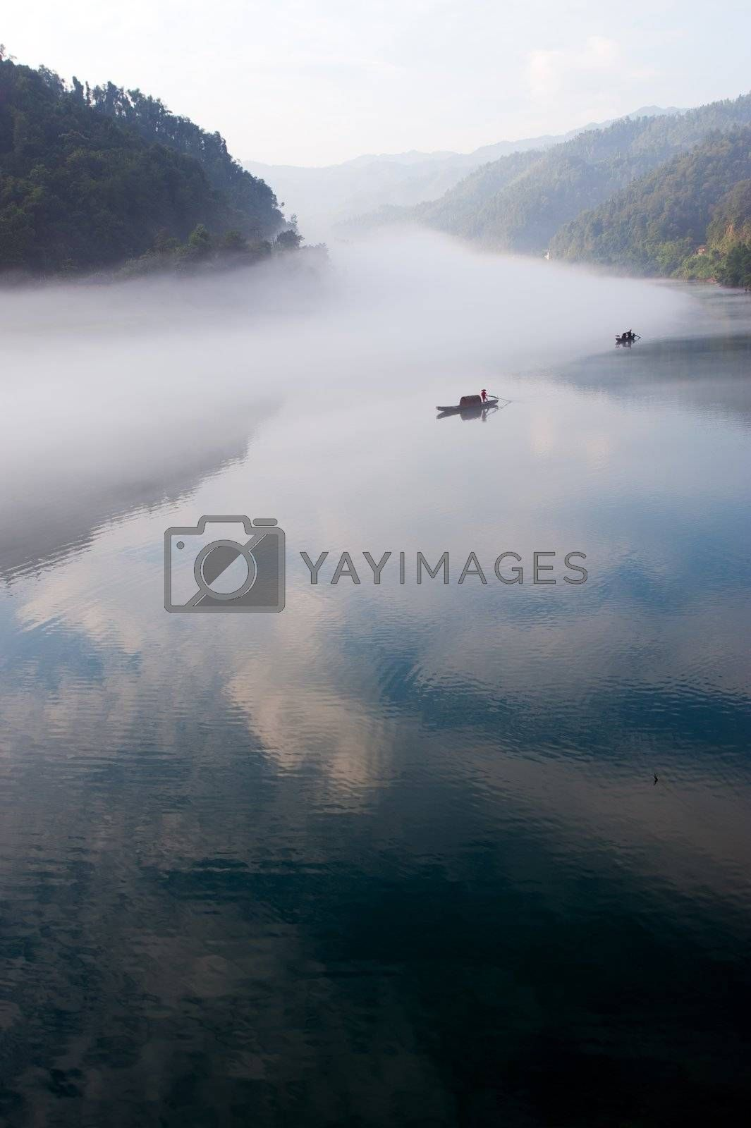 Fishing boat on the foggy river in Hunan province of China