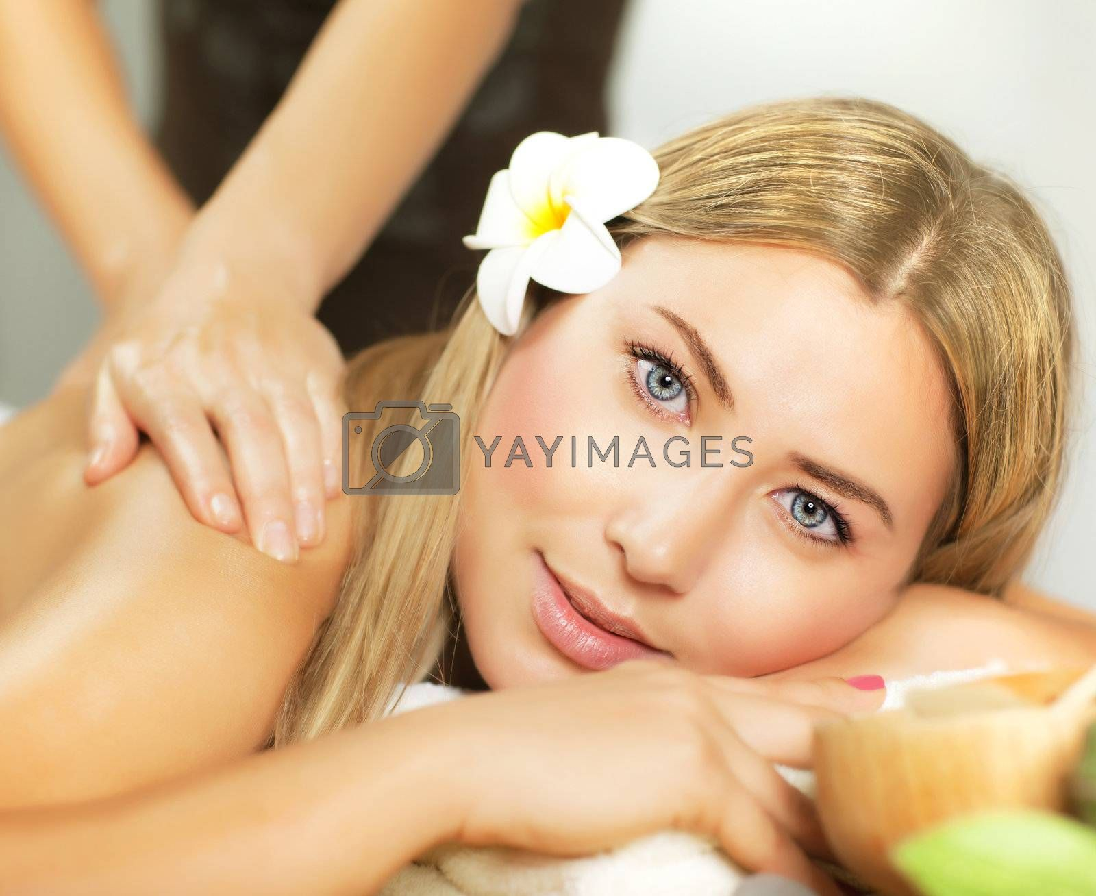 Photo of pretty woman enjoying day spa, cute female lying down on massage table, frangipani flower in hair, alternative treatment, natural cosmetics, luxury spa salon, health care and beauty concept