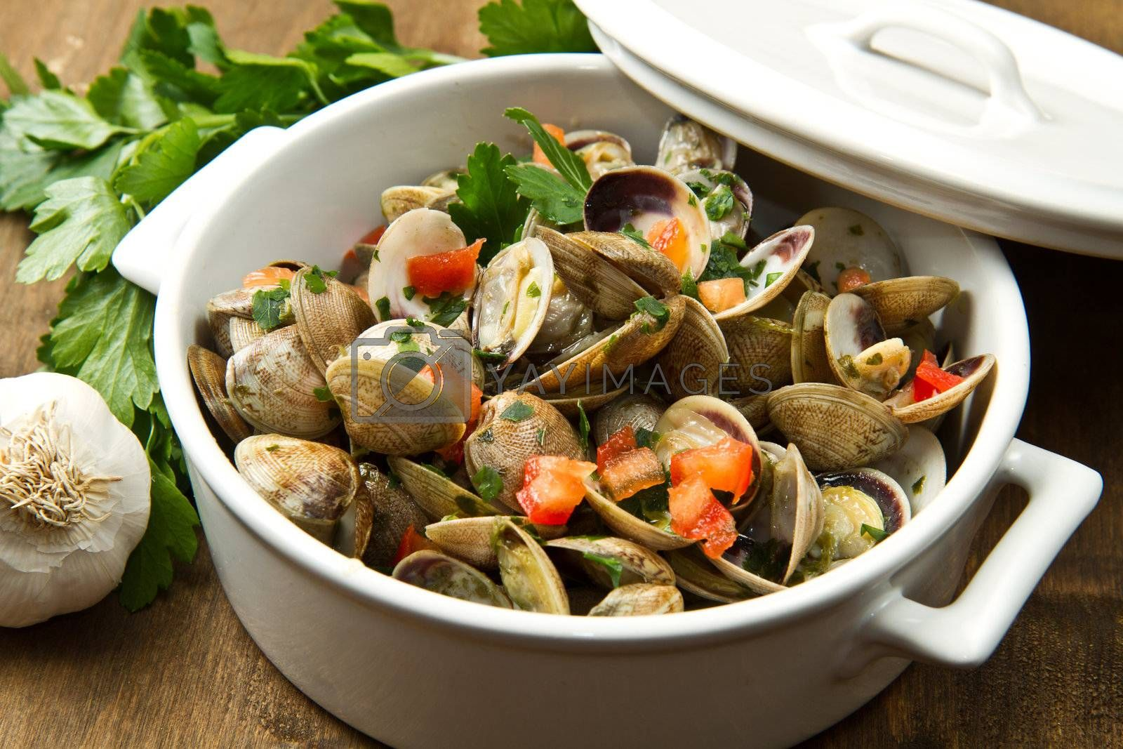 a delicious clams soup with tomatoes on wooden table