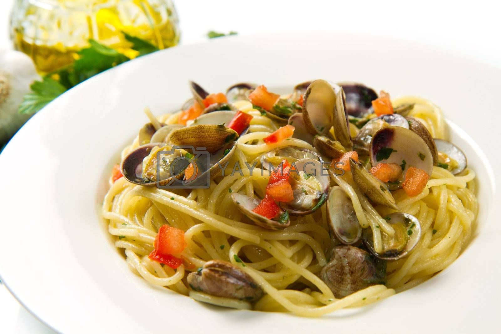 white dish of spaghetti,clams , tomatoes, oil and parsley