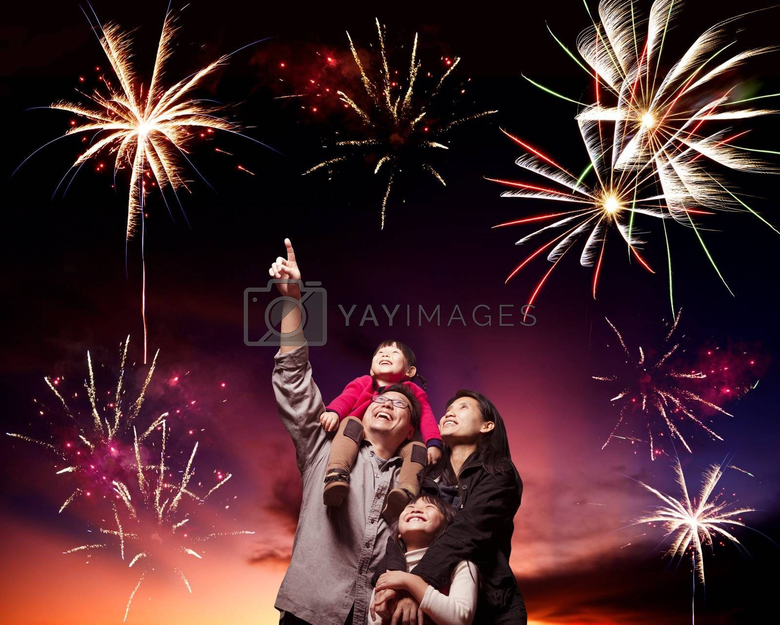 happy family looking fireworks in the evening sky