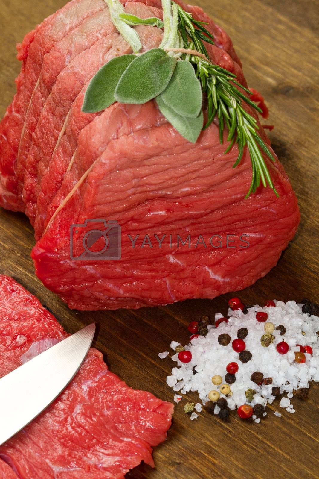 Raw beef on wooden table with rosemary ,sage and salt