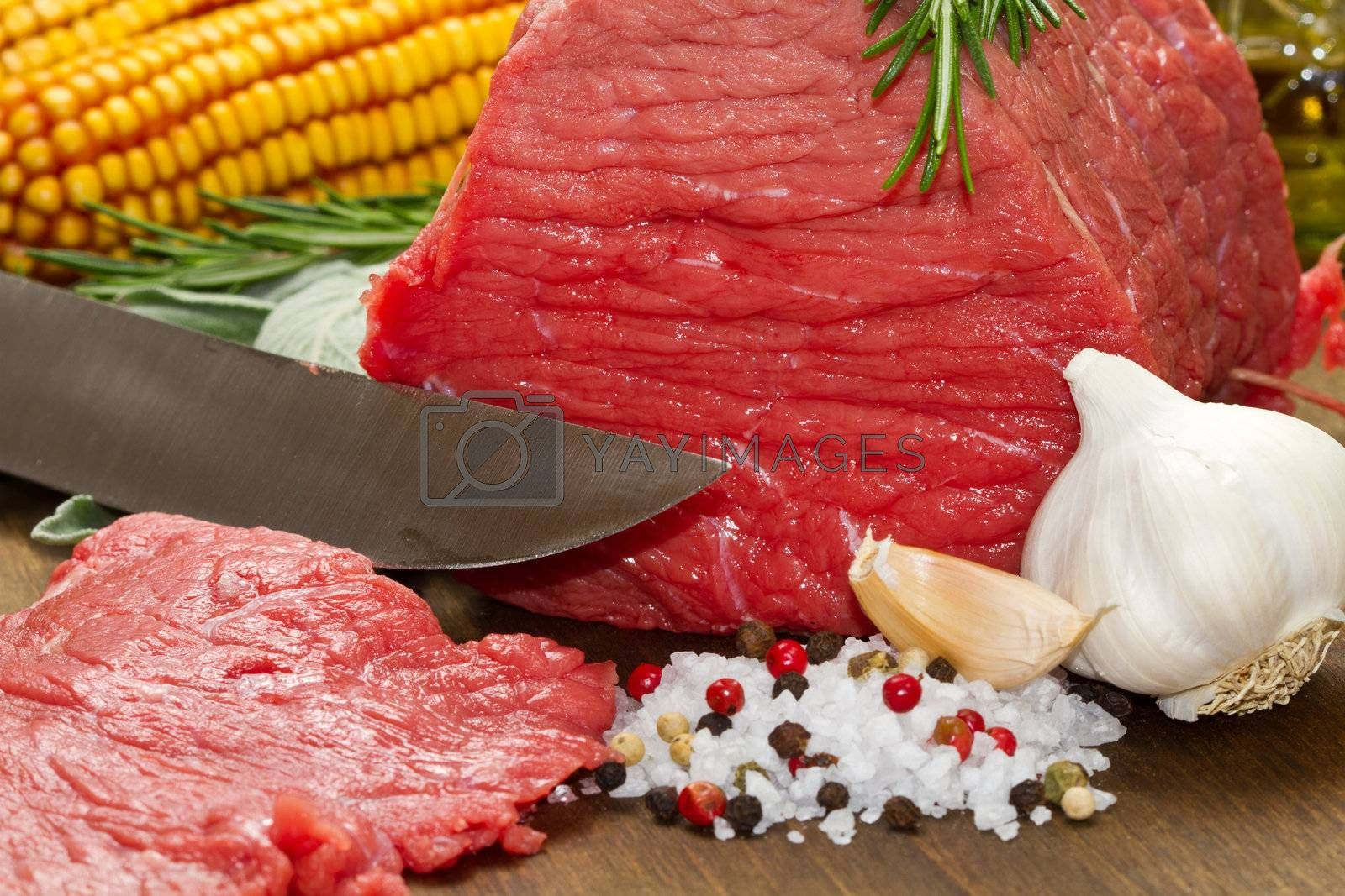 Raw beef on wooden table with rosemary ,sage , salt, cob and garlic