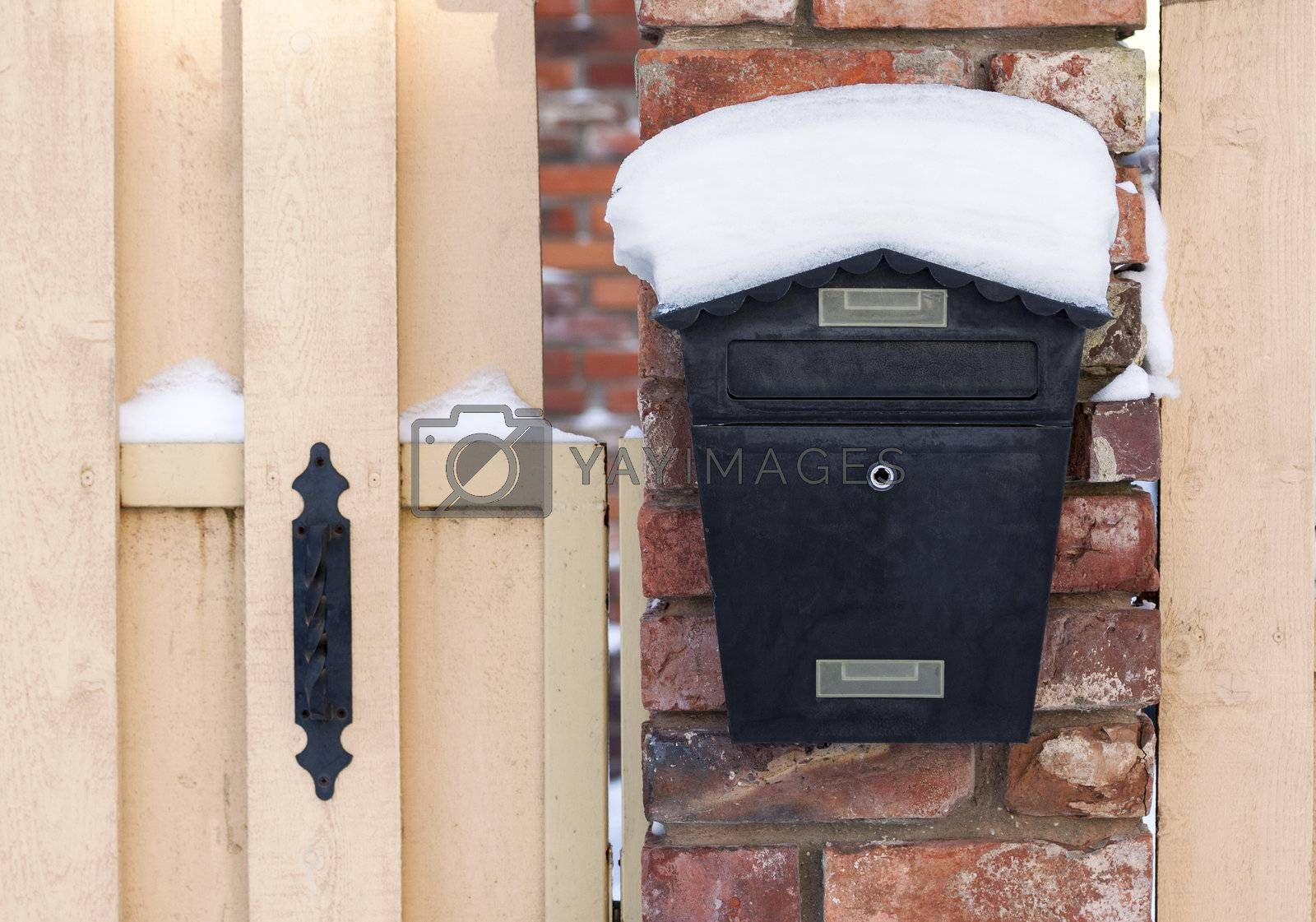 Black mailbox covered with snow outside residential house