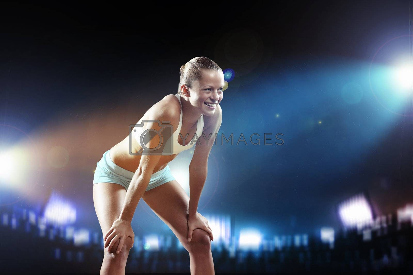 Fitness woman standing against stadium lights background