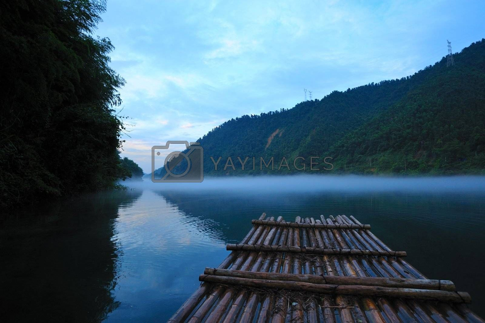 River landscape at sunset with fog rolling across the chilly river water, photo taken in Hunan province of China