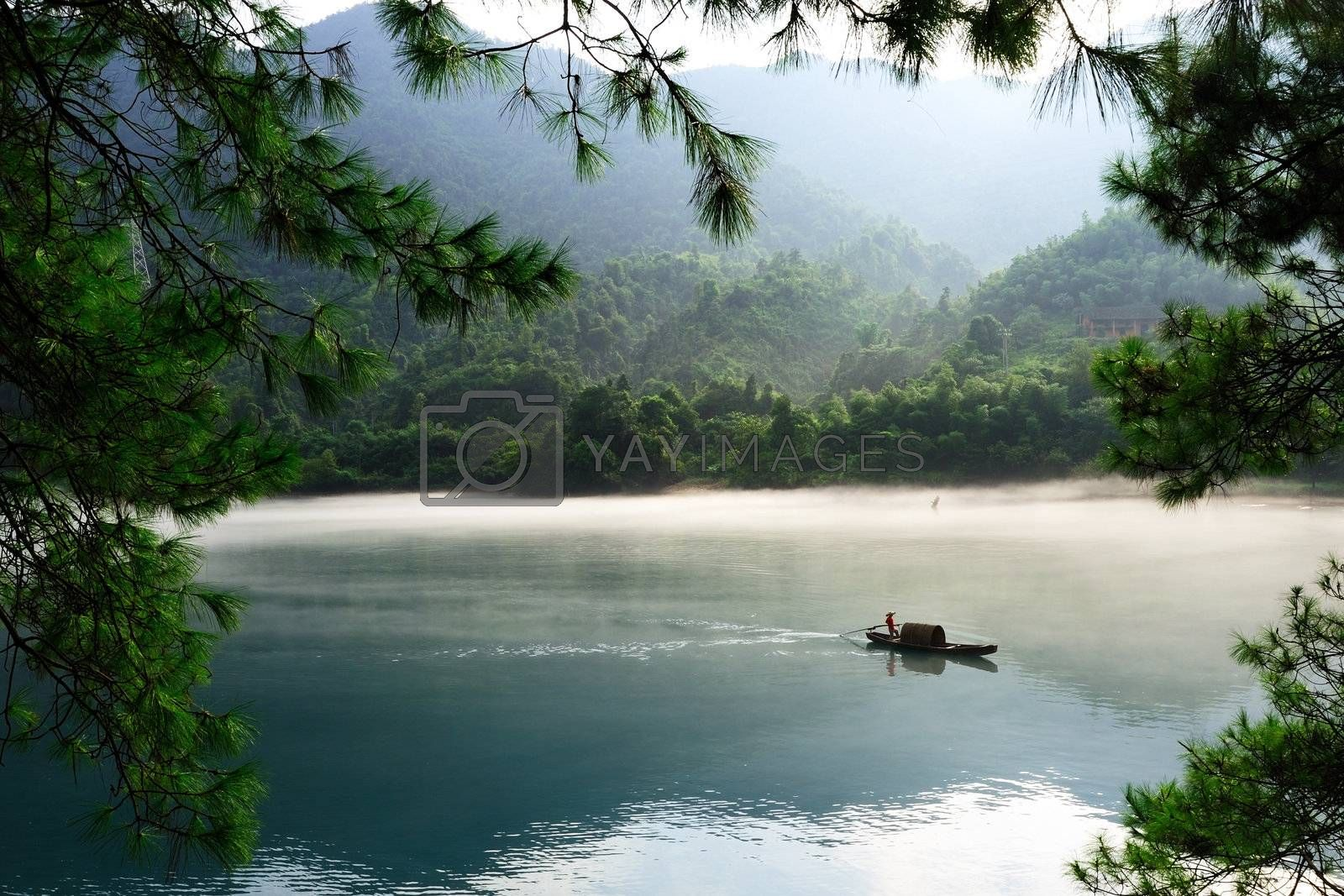 Fishing boat on the foggy river with tree branch as the foreground, in hunan province of China