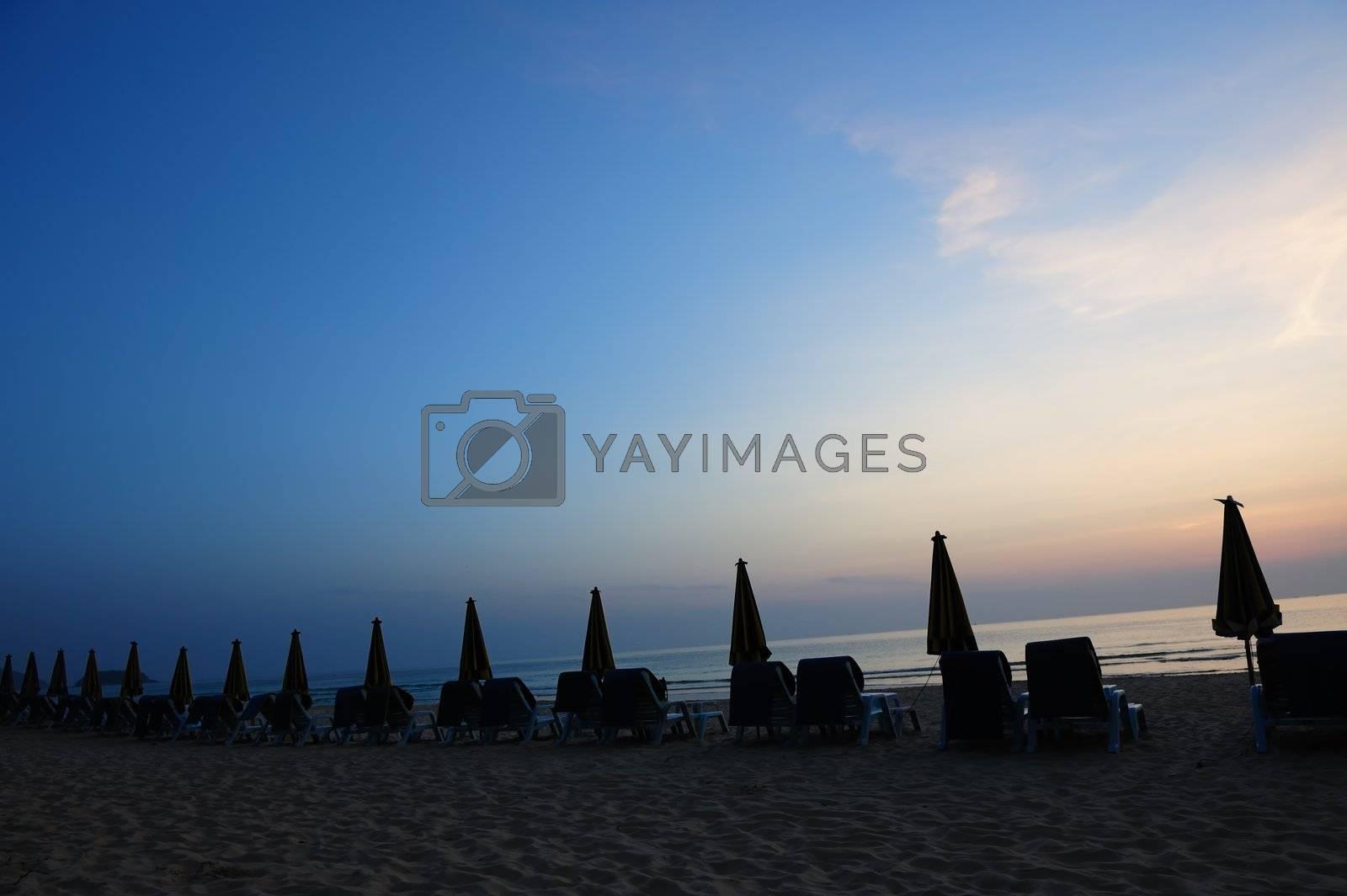 Beach landscape with a row of folded umbrella in Phuket Island, Thailand