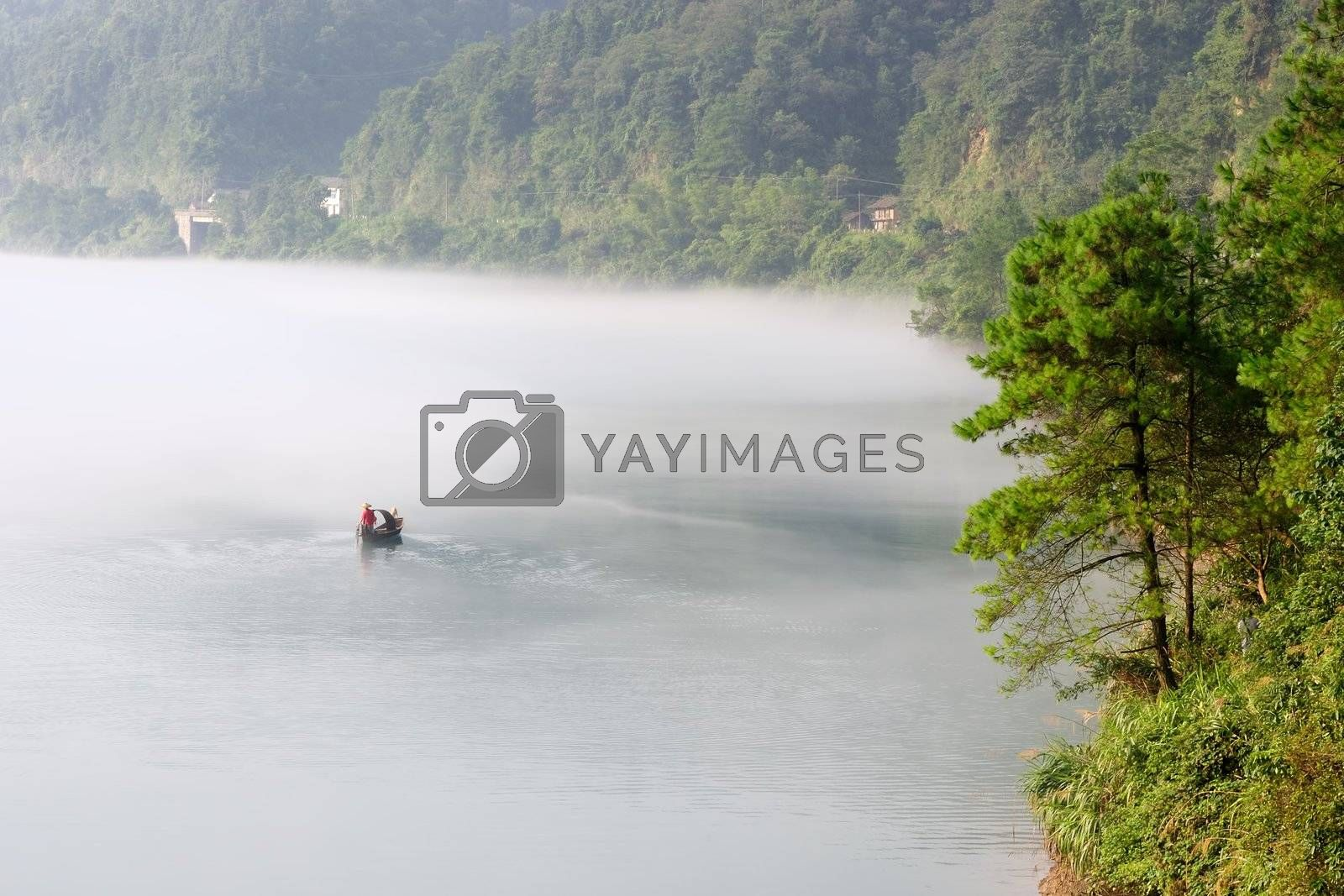 Morning fog rolls across the chilly river water, photo taken in hunan province of China