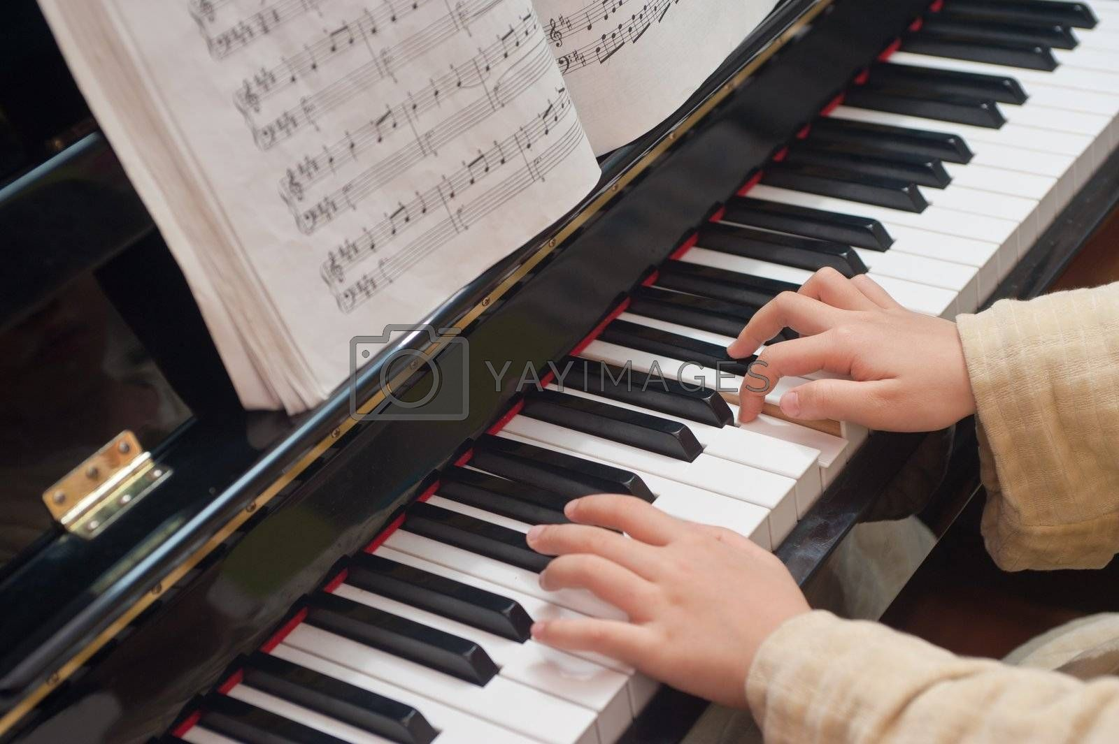 Hands of a little Asian kid learning to play piano