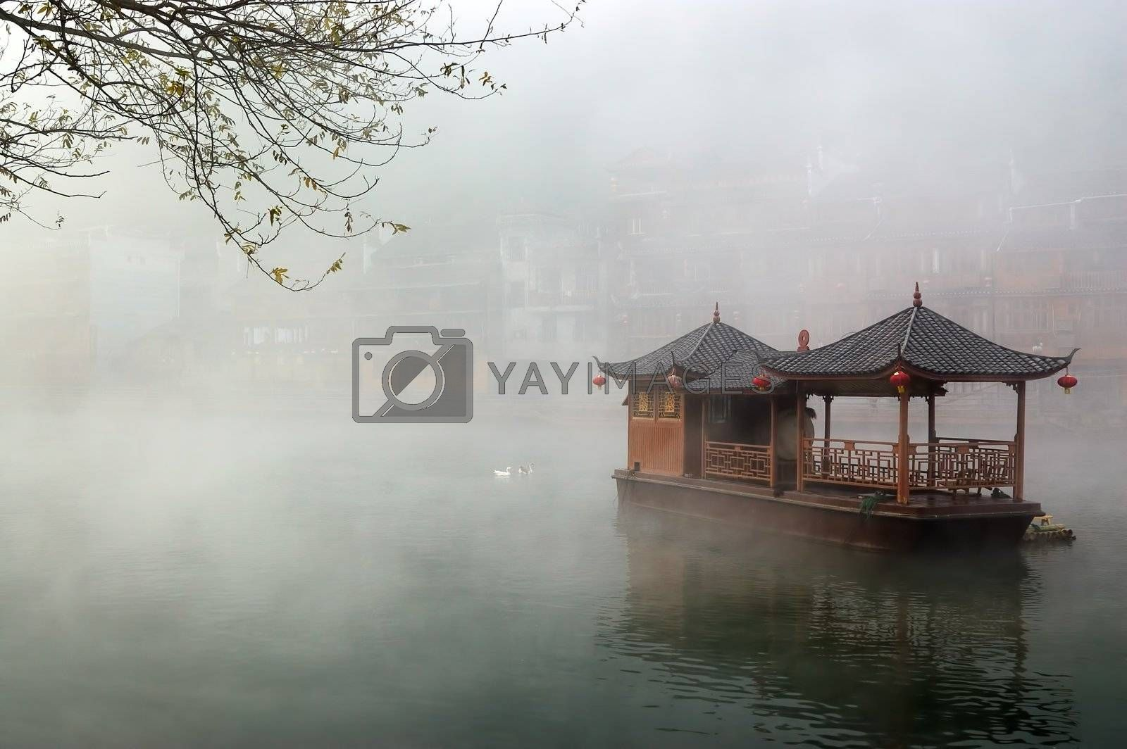 China landscape of boat on foggy river with traditional building background in Hunan province