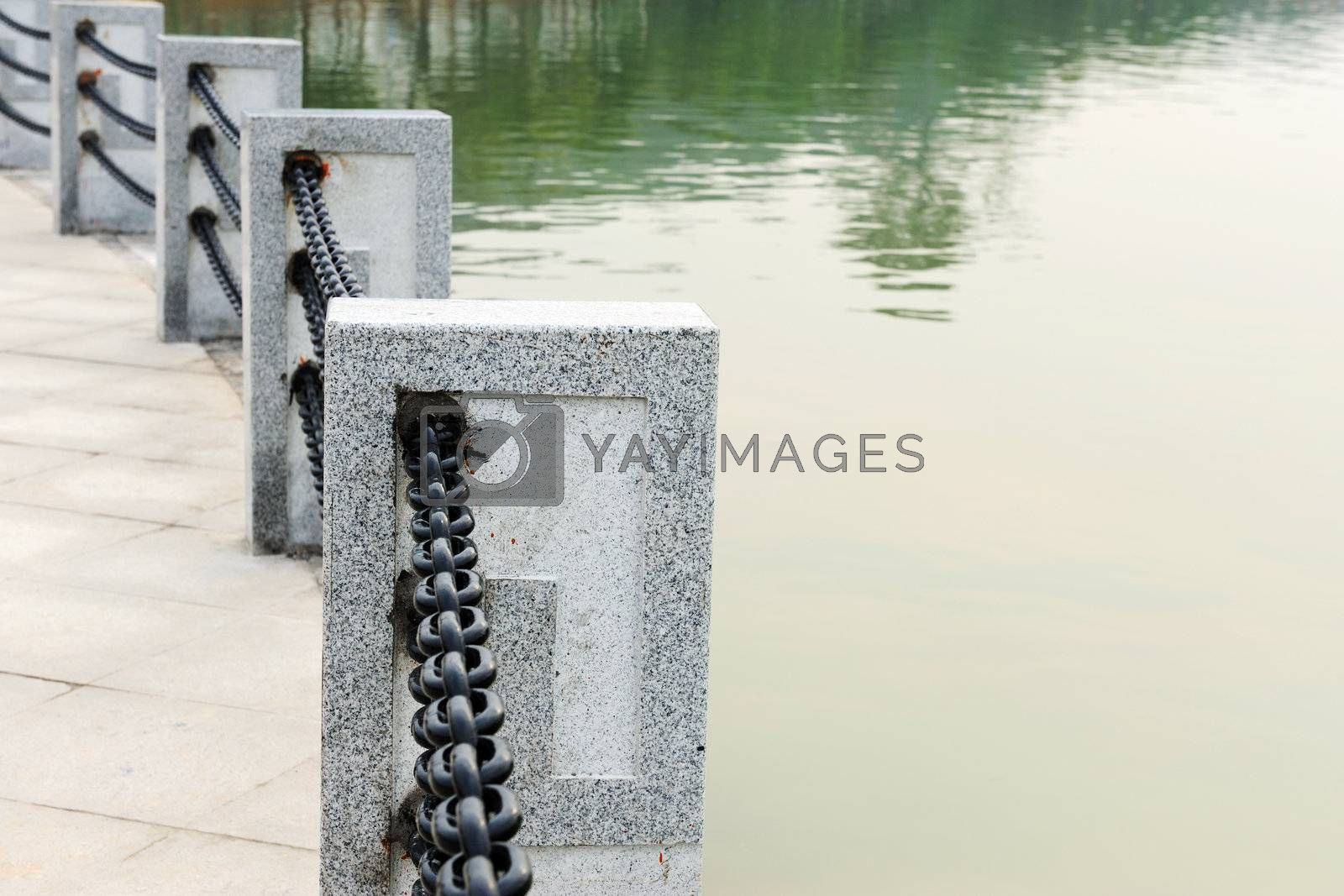 Handrail by the lake made of stone and iron trail