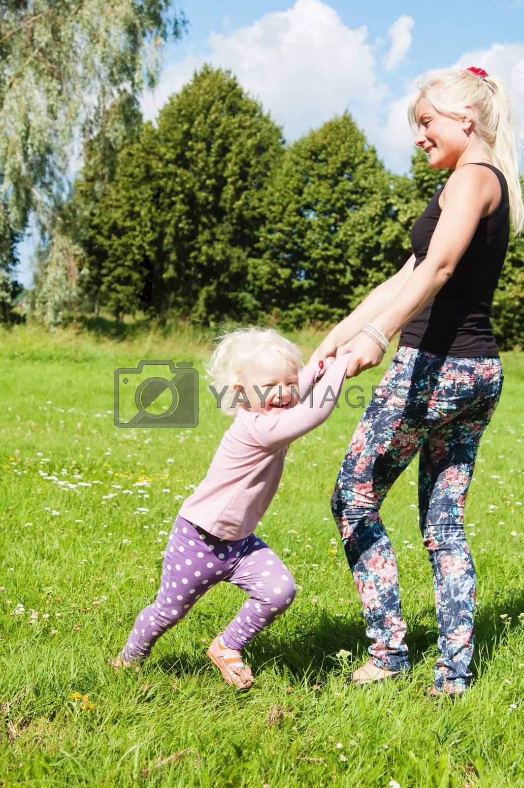 Mum with a daughter play to a glade by breeze09