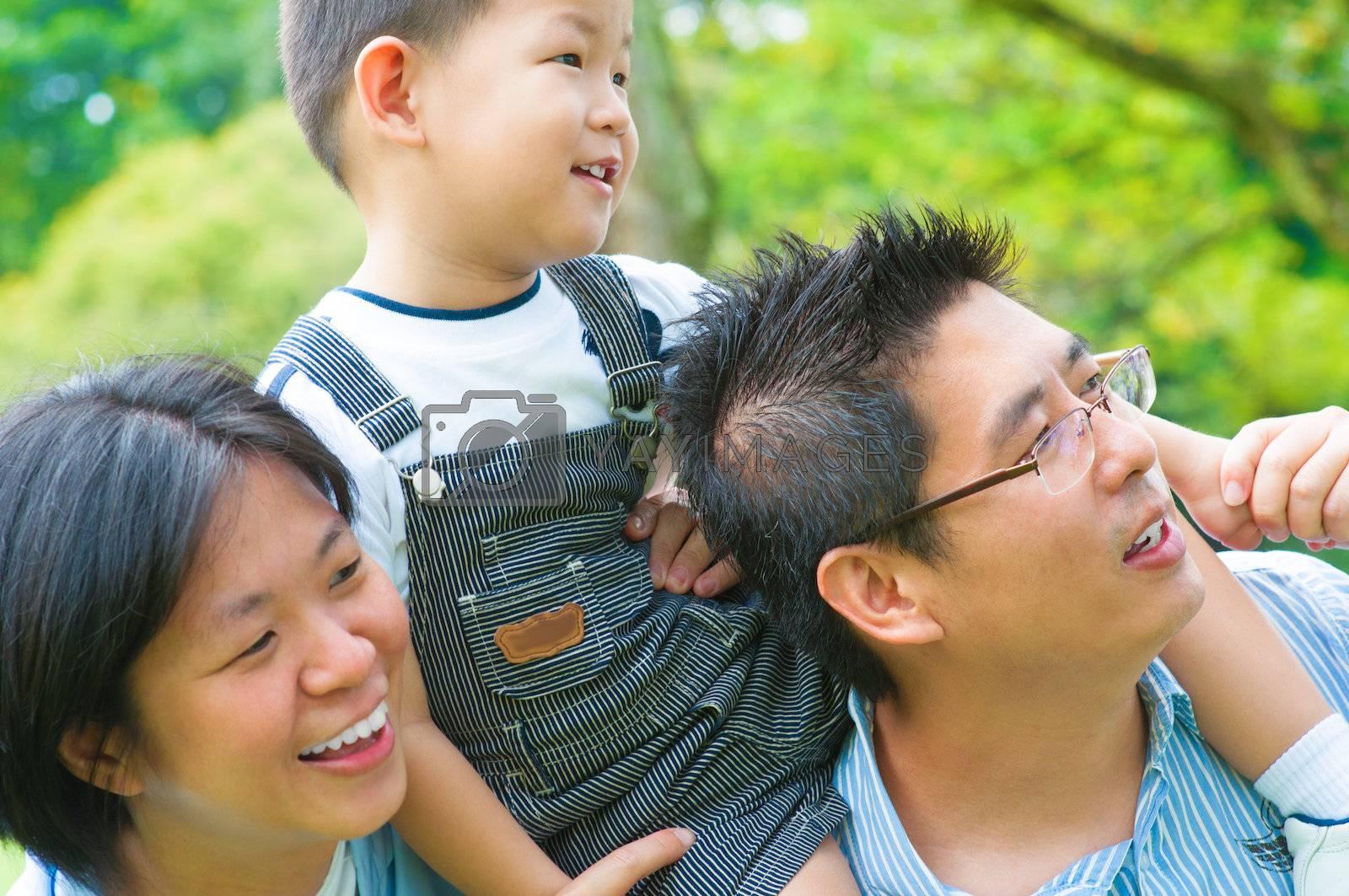 Happy Asian family having fun outdoor green park