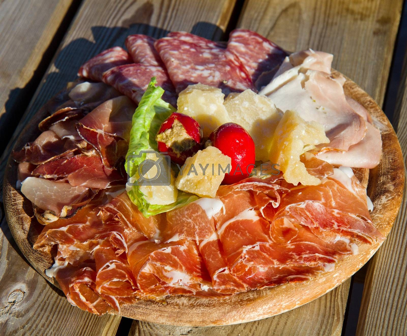 a platter of mixed cured meats, cheese on wood table