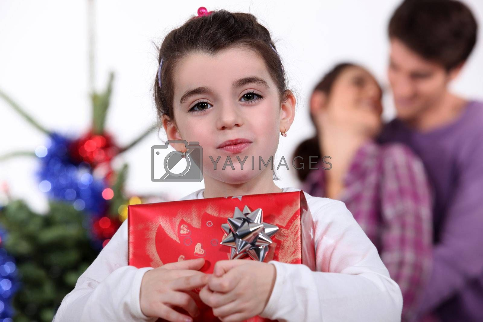 Young girl holding a gift on Christmas Day by phovoir