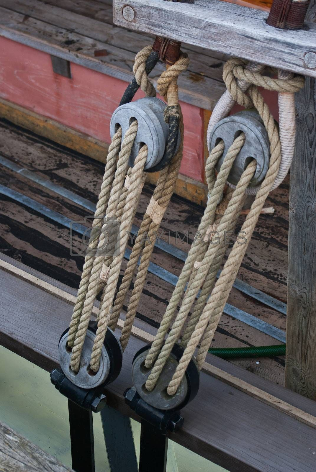 Nautical ropes and vintage wooden pulley on a sail boat sailing background image